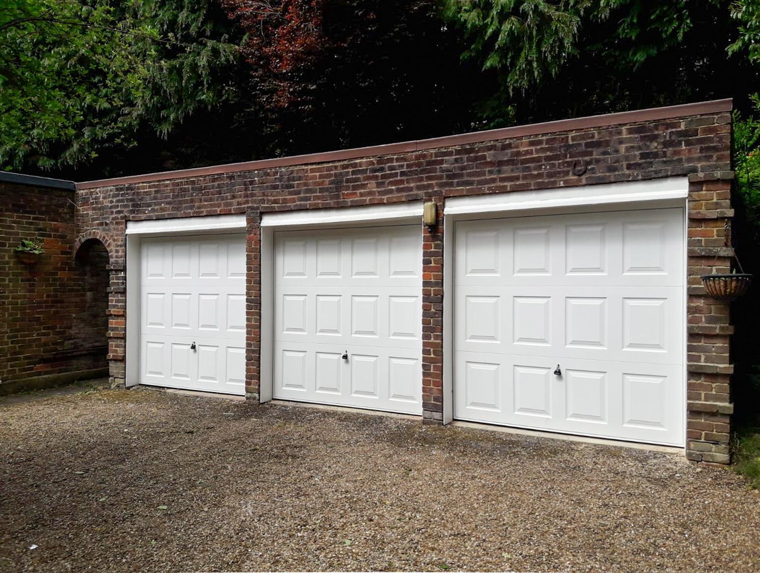 A trio of Garador Georgian up and over garage doors in white